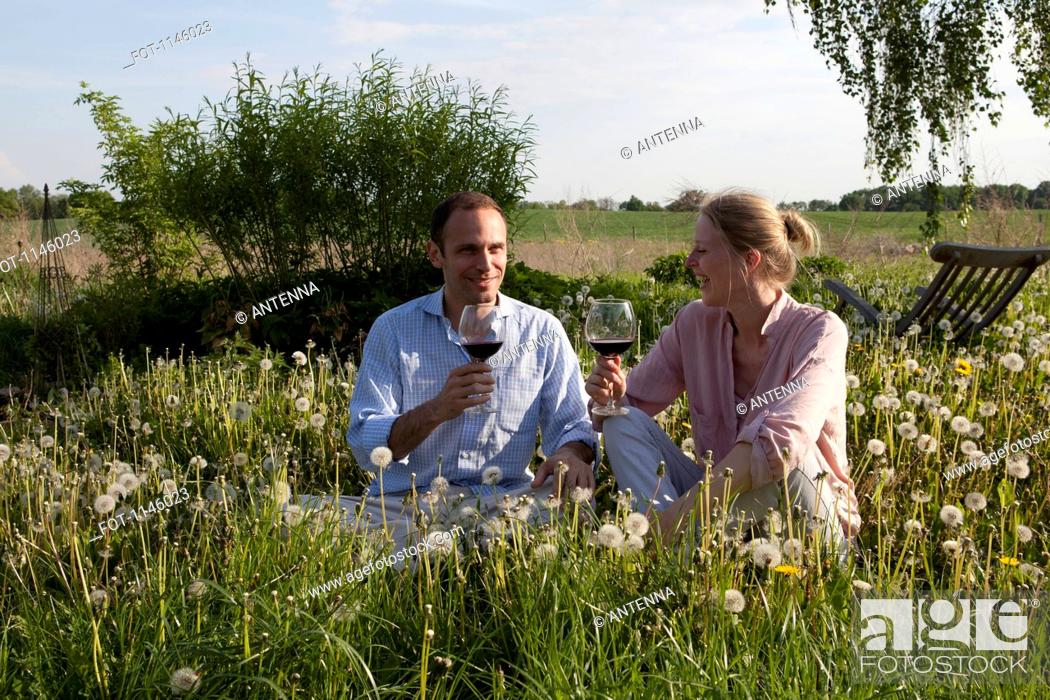 Stock Photo: A couple sitting in the grass enjoying some red wine.