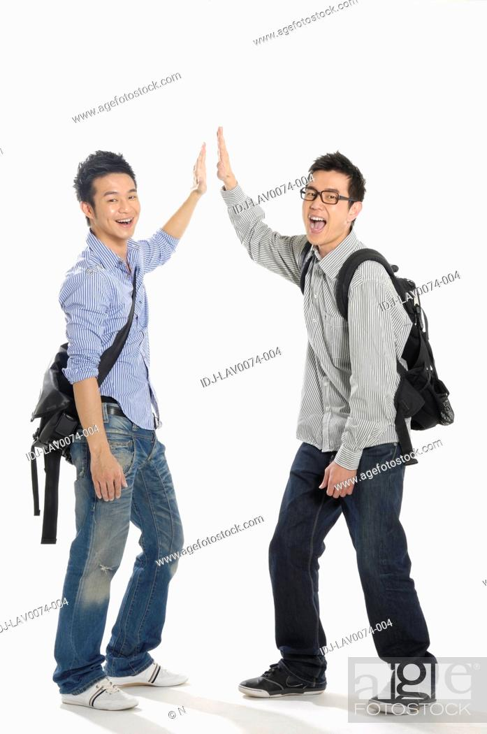 Stock Photo: Male university students giving high-five to each other.