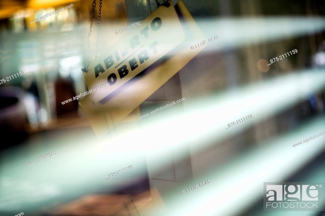 Stock Photo: Ad in a door shop with the words Abierto - Obert, seen from a blinds of a shop in Barcelona, Spain, Europe.