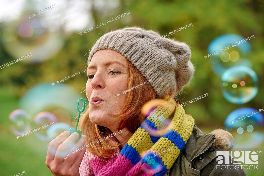 Stock Photo: Woman blowing rainbow bubbles.