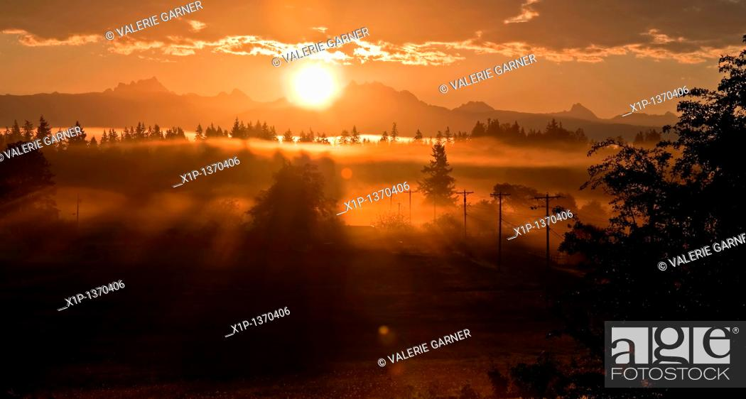 Stock Photo: This stunning sunrise is coming over the mountain known as 3 Sisters or 3 Fingers called both commonly in Washington state  A heavy fog is laced in and.