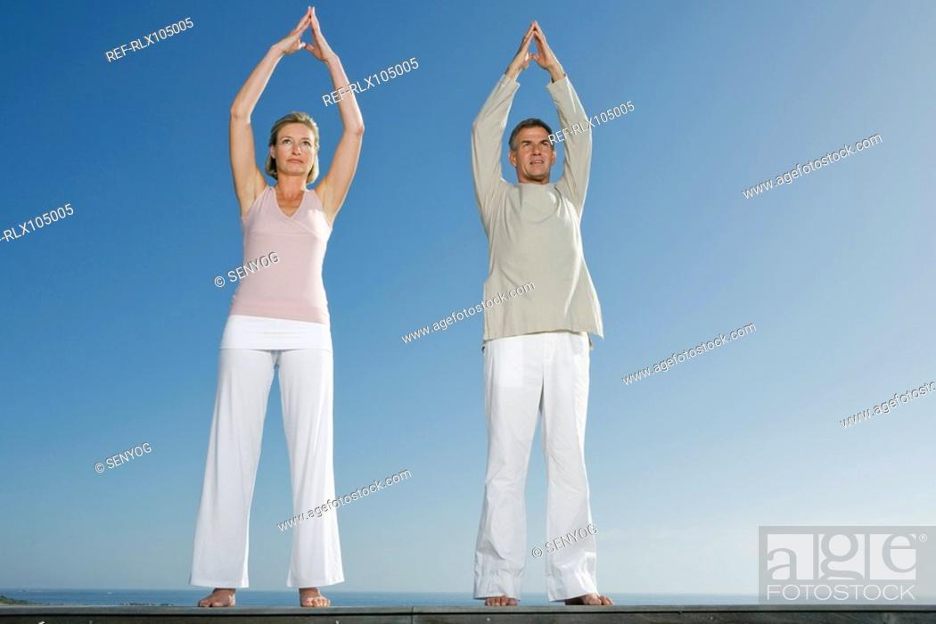 Stock Photo: Mature couple standing on wooden bench outdoors doing yoga exercises.