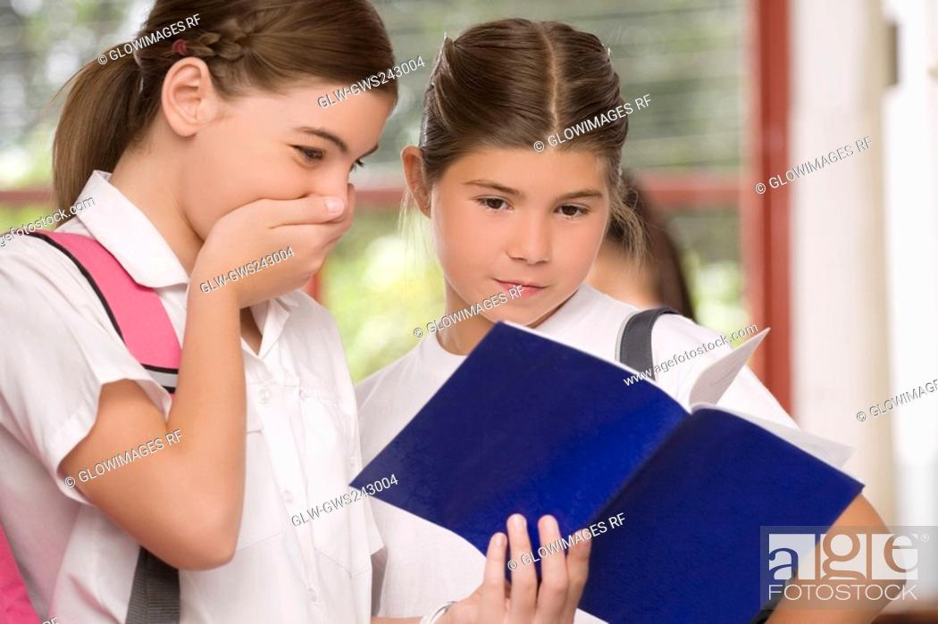 Stock Photo: Close-up of a schoolgirl showing her textbook to another schoolgirl.