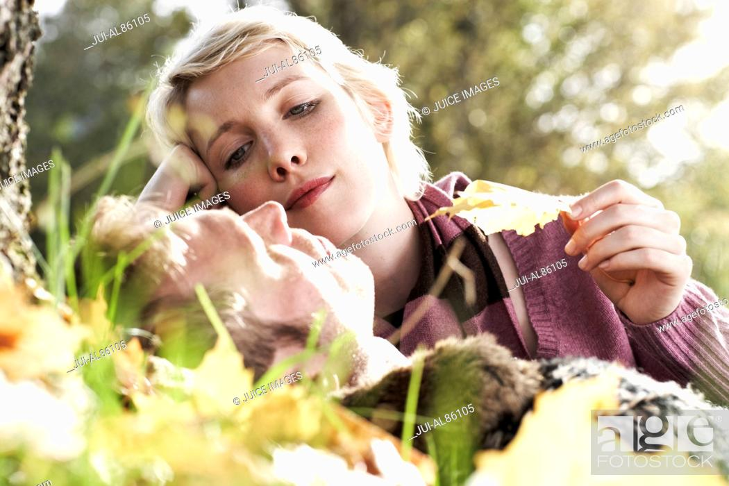 Stock Photo: Woman looking at boyfriend sleeping in grass outdoors.