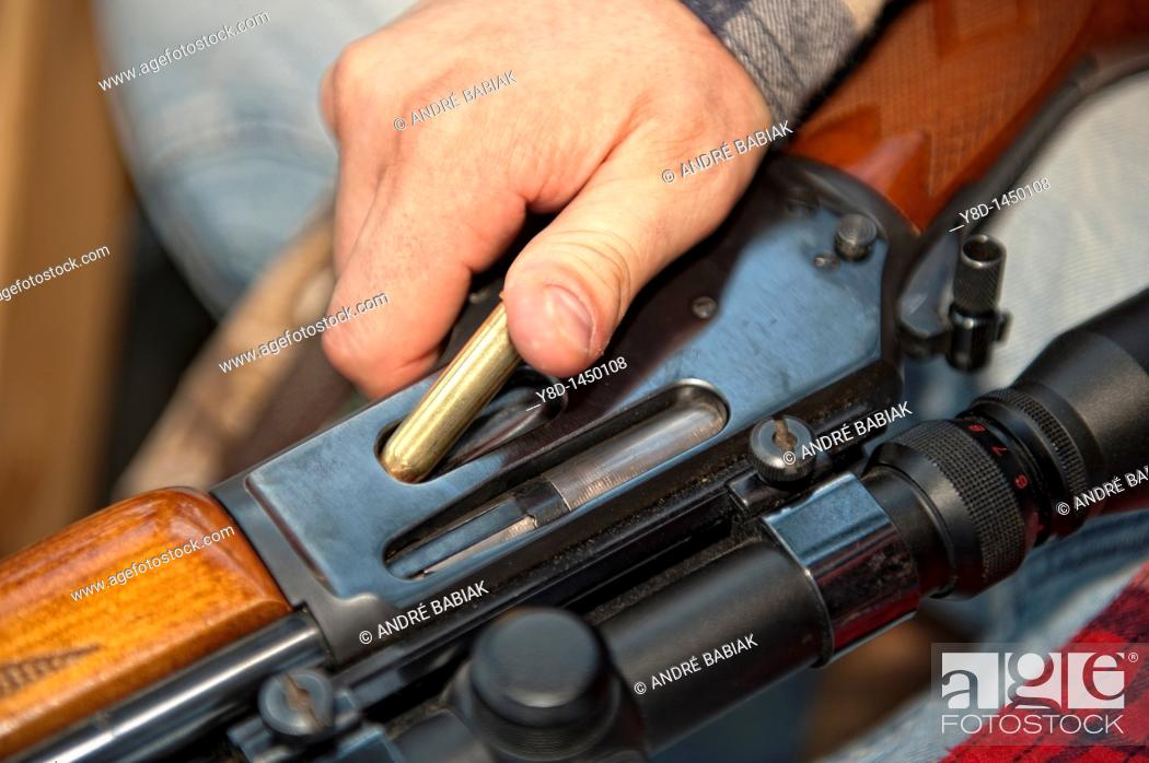 Stock Photo: Hunter loading firearm hunting rifle with ammunition cartridge.