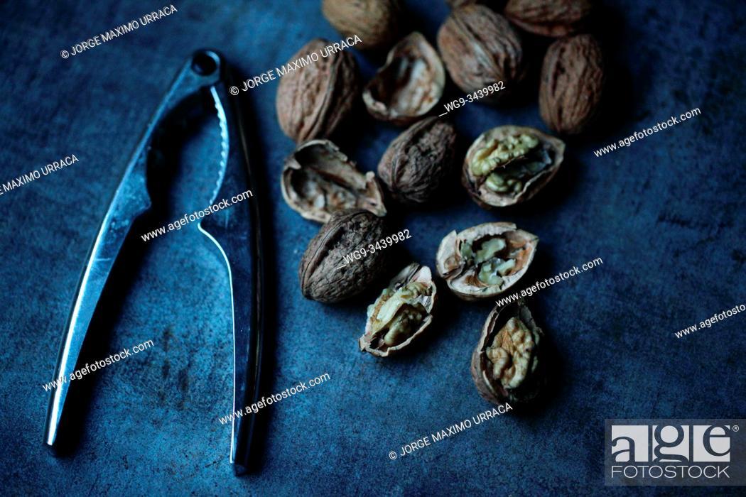 Stock Photo: Walnuts and nutcracker.