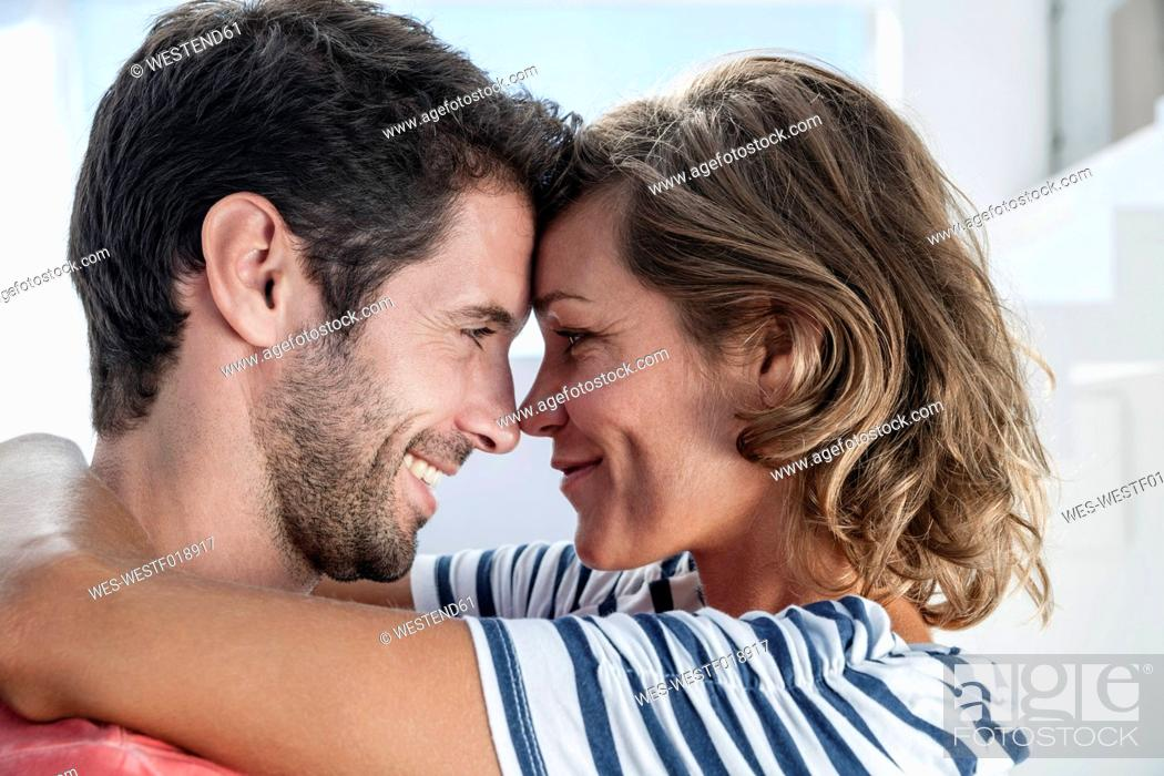Stock Photo: Spain, Mid adult couple embracing each other in modern apartment.
