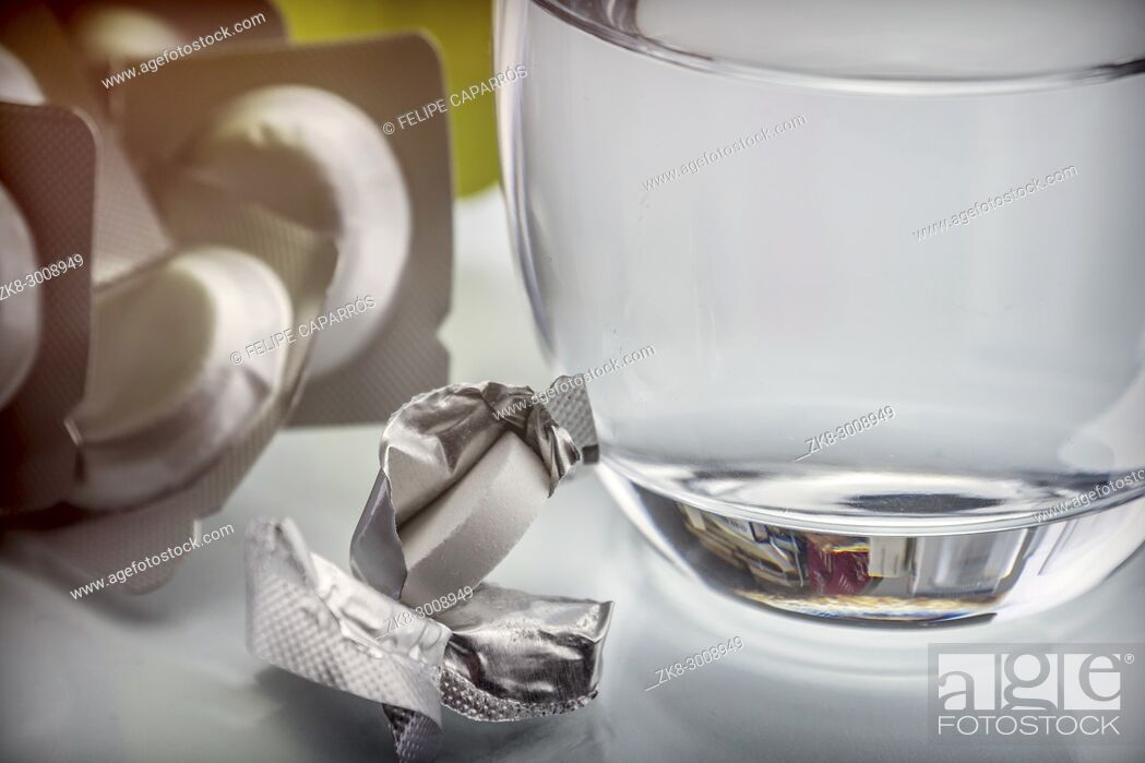 Stock Photo: Glass of water next to an effervescent pill, conceptual image.