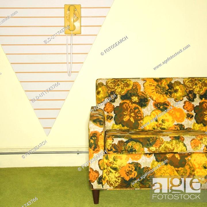Stock Photo: Retro floral printed sofa with yellow rotary phone hanging on wall.