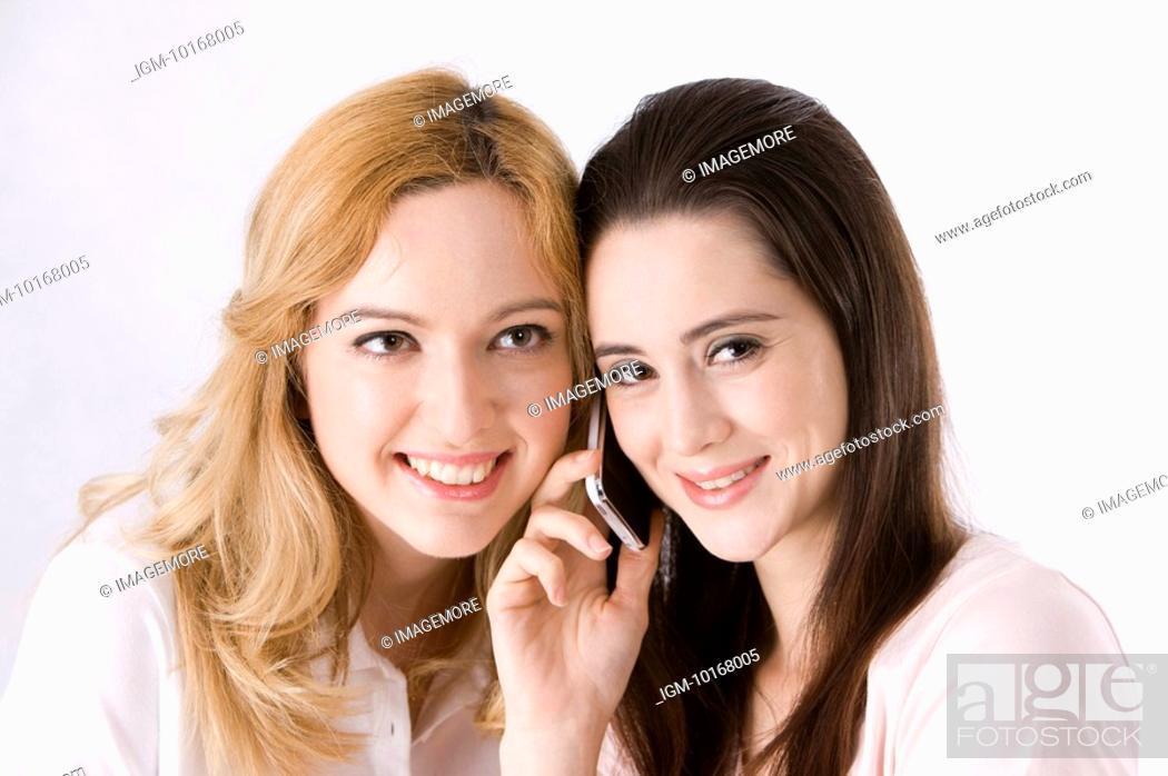 Stock Photo: Two young women listening to one mobile phone.