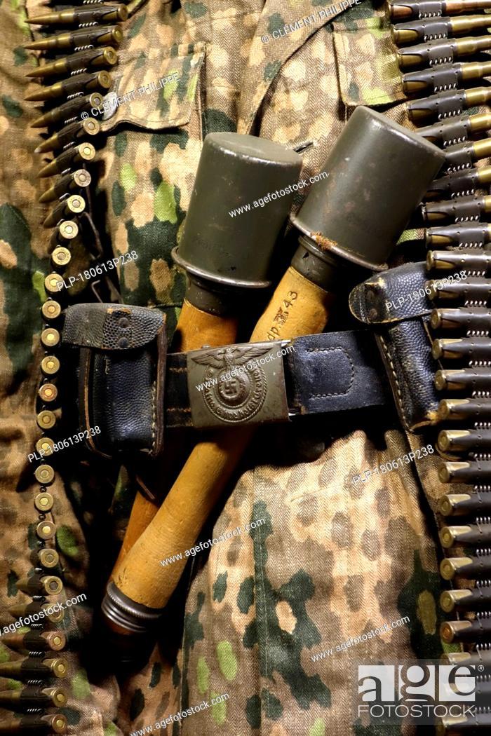 Stock Photo: Close up of two WW2 stielhandgranaten tucked under pants belt of German SS soldier carrying machine gun ammunition belt.