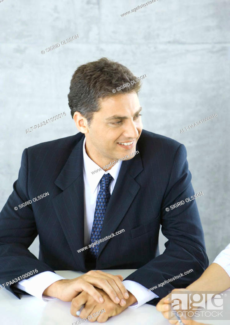 Stock Photo: Businessman sitting at table, smiling at colleague.