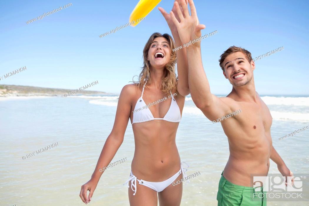 Stock Photo: Couple catching plastic disc on beach.