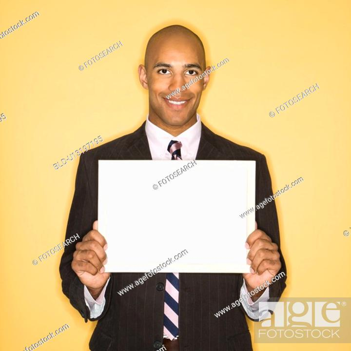 Stock Photo: Man smiling holding blank sign against yellow background.