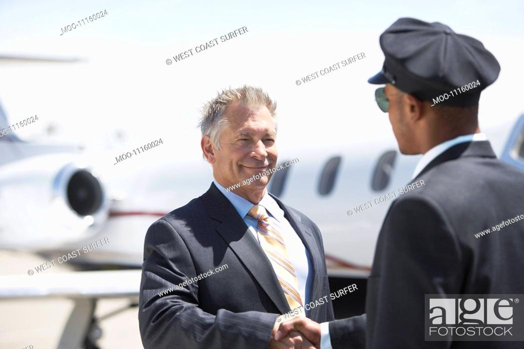 Stock Photo: Businessman Beside private jet shaking hands with pilot.