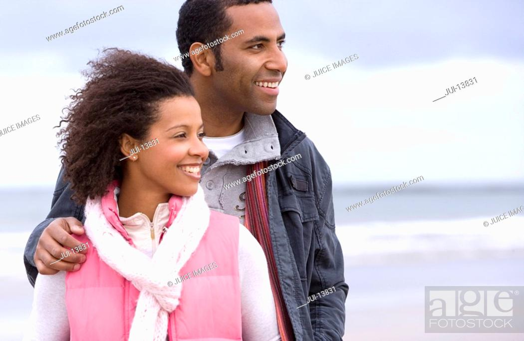 Stock Photo: Young couple on beach, man with hand on woman's shoulder, smiling.
