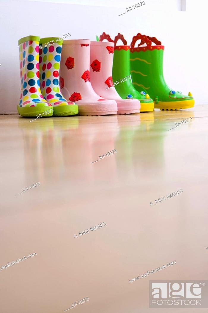 Stock Photo: Three pairs of children's rubber boots, ground view.