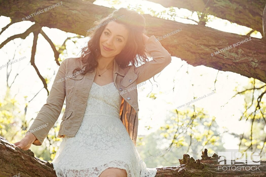 Stock Photo: Portrait of smiling young woman sitting on a branch in a park at backlight.