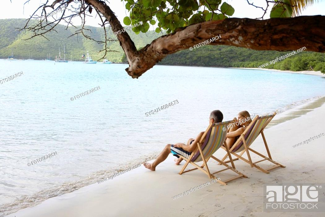 Stock Photo: Mid adult couple on lounge chairs on beach high angle view, St. John, US Virgin Islands, USA.