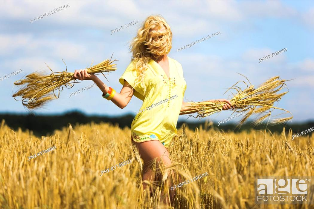 Stock Photo: Young woman holding wheat in a field.