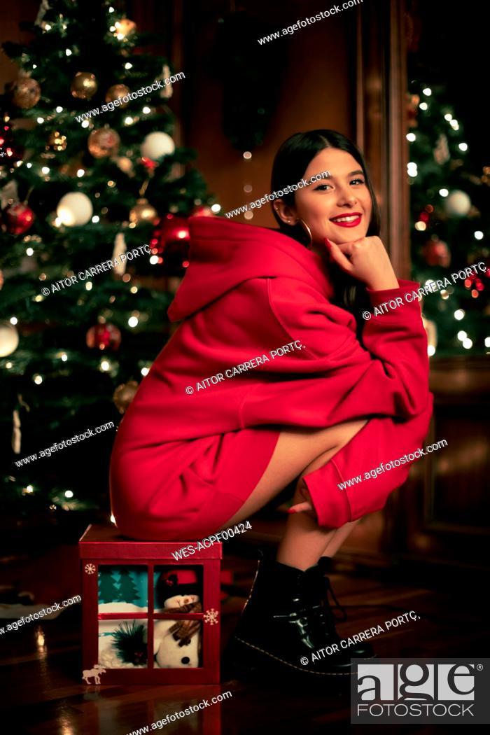 Stock Photo: Portrait of smiling teenage girl sitting on Christmas present.