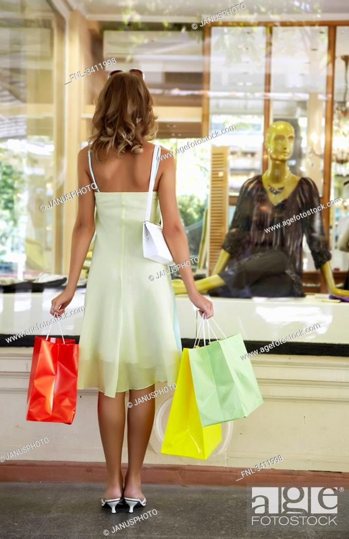 Stock Photo: Young woman standing with shopping bags in front of a shop window.