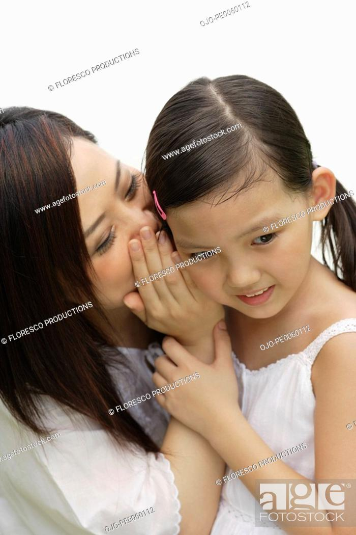 Stock Photo: Woman indoors whispering in young girl's ear.