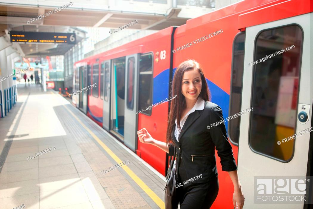 Stock Photo: Businesswoman in Docklands Light Railway train, London.