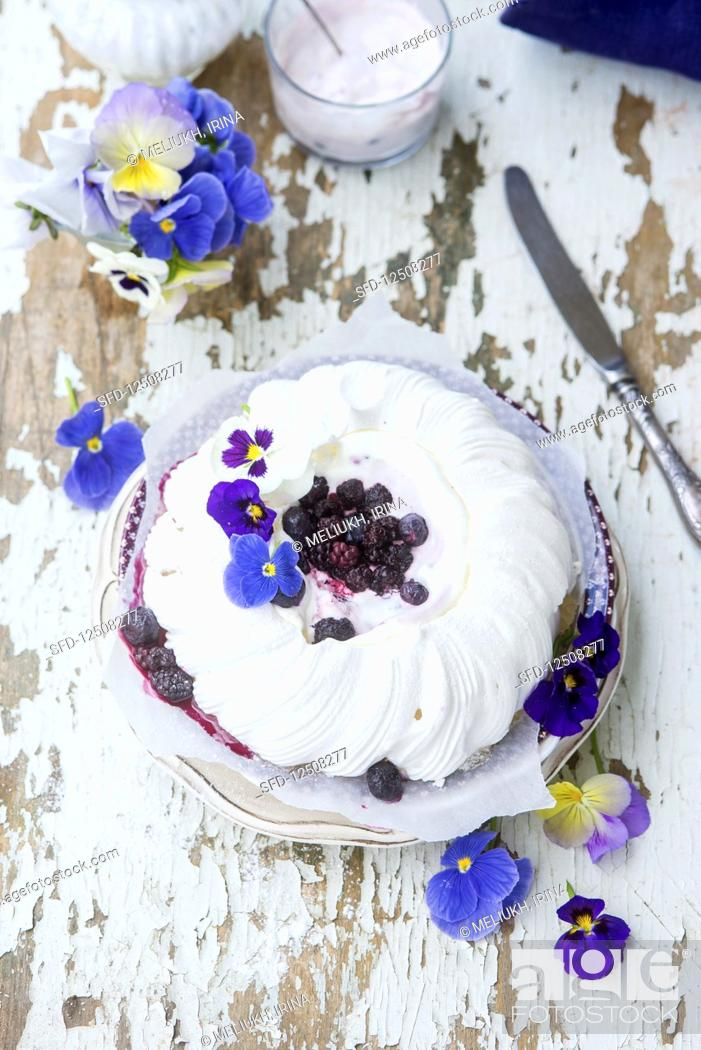 Stock Photo: A festive pavlova with berries and pansies.