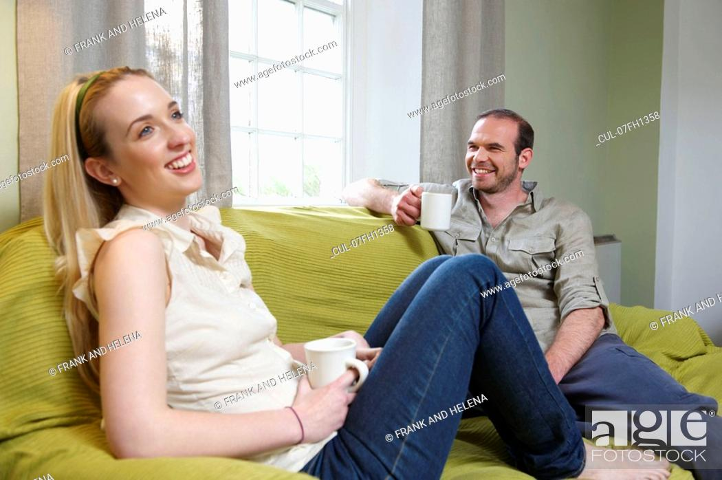 Stock Photo: Couple sitting on couch, with mugs.