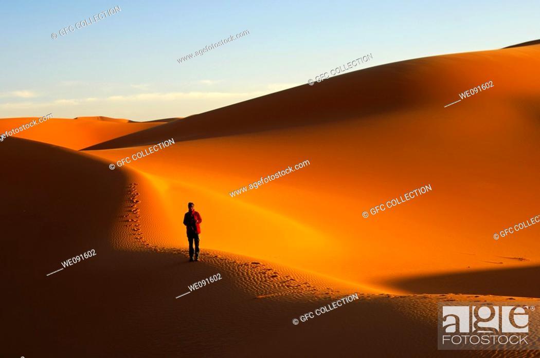 Stock Photo: Tourist walking at sunset in the sand dunes of the Erg Muzuruq, Sahara desert, Libya.