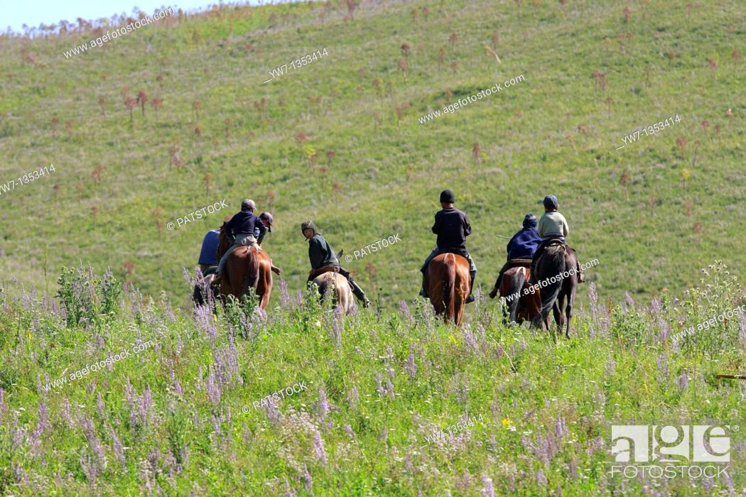 Stock Photo: Kyrgyz boys riding their horses that are central to the traditional Kyrgyz way of life and it is natural to see many children on horseback.