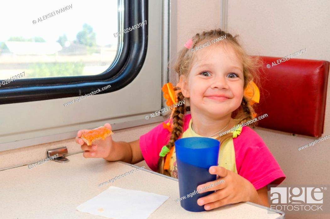 Stock Photo: Little girl with a happy face drink tea with a sandwich on the train at the table on outboard second-class carriage.