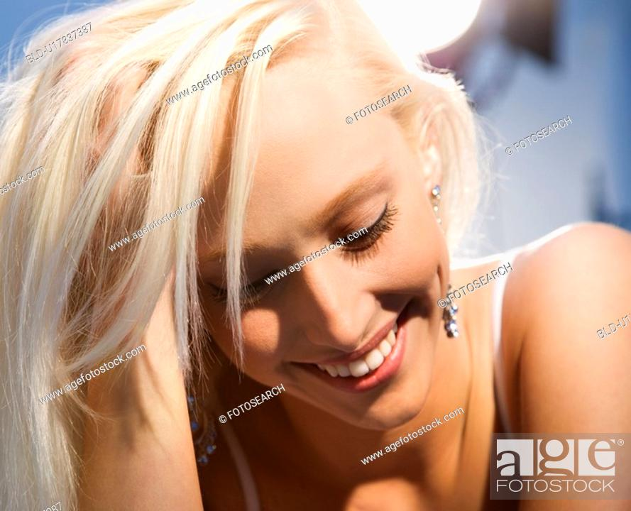 Stock Photo: Portrait of attractive blonde Caucasian young adult woman smiling and looking down.