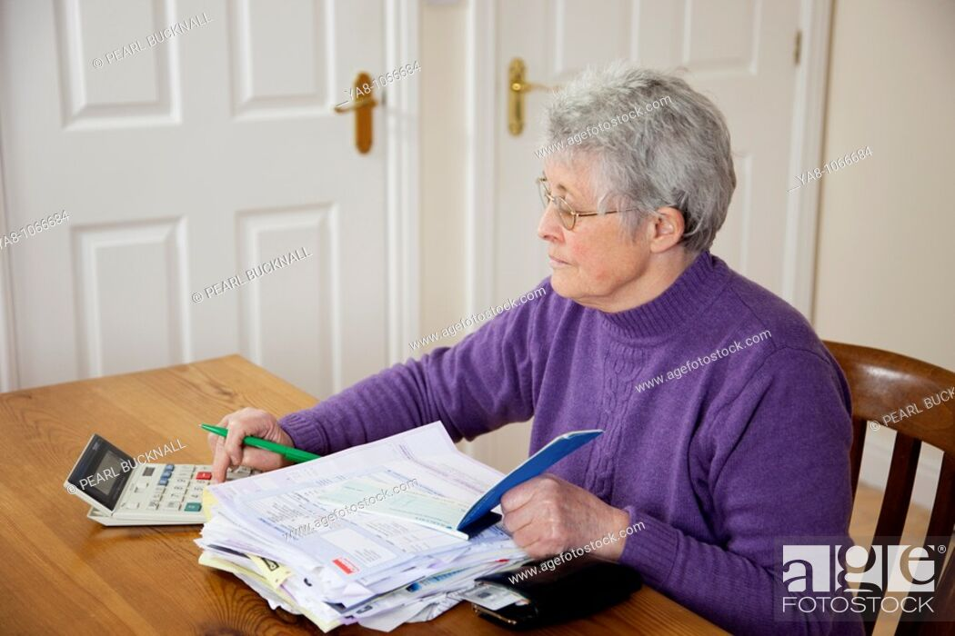 Stock Photo: Britain, UK, Europe  Senior woman pensioner with a big pile of bills on the table using a calculator before writing a cheque.