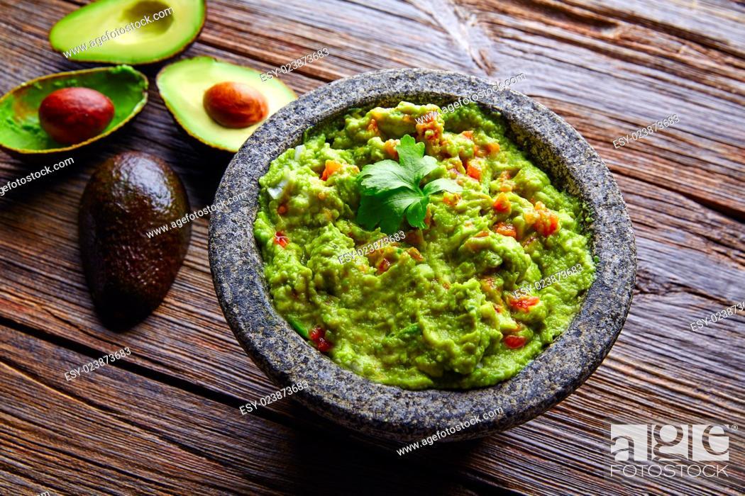 Photo de stock: avocado Guacamole on molcajete real Mexican traditional procedure.
