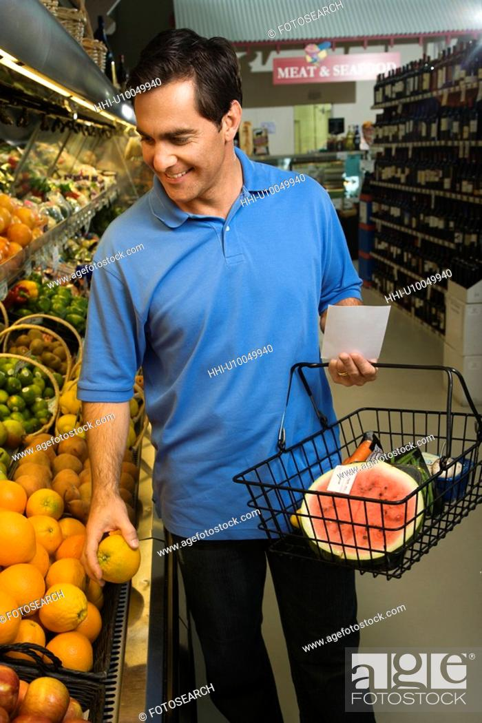 Stock Photo: Caucasian mid-adult male grocery shopping for fruit.