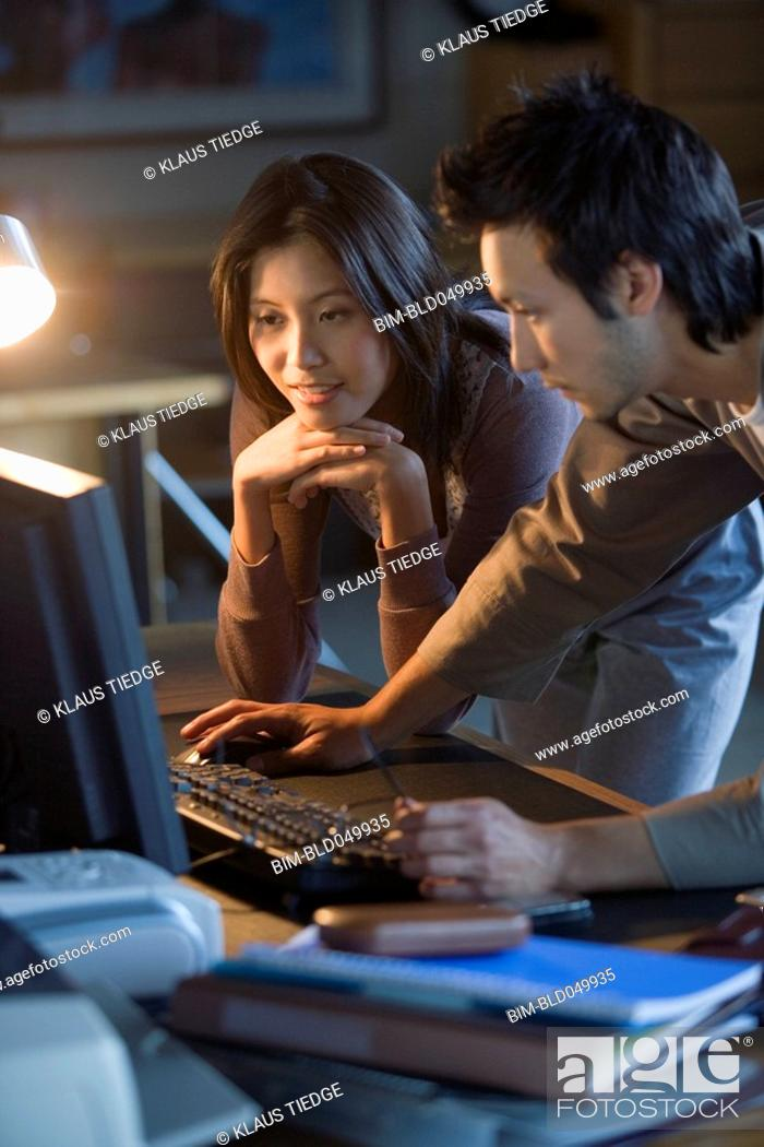 Stock Photo: Asian businesspeople looking at computer.