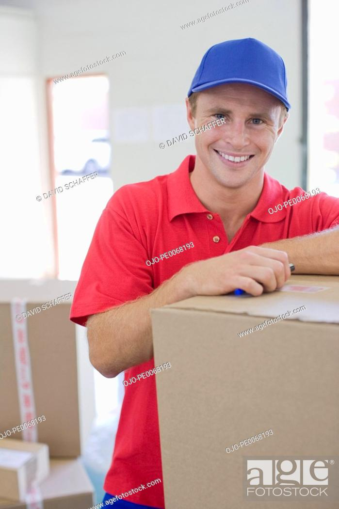Stock Photo: Delivery man leaning on cardboard box in warehouse.