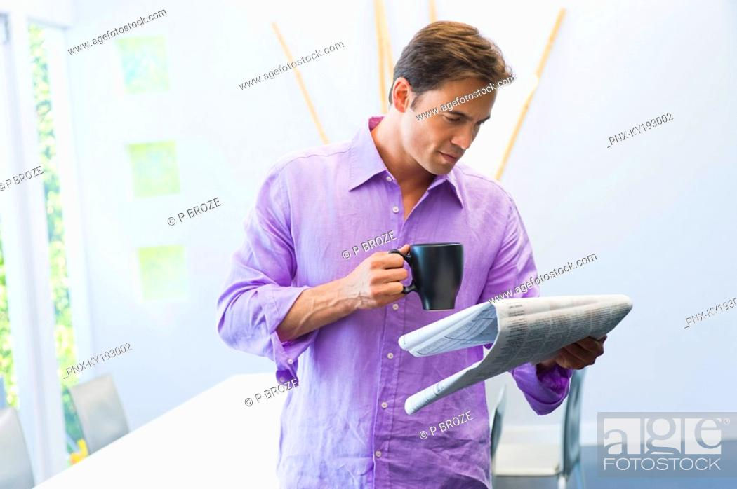 Stock Photo: Man reading a newspaper and drinking a cup of coffee.