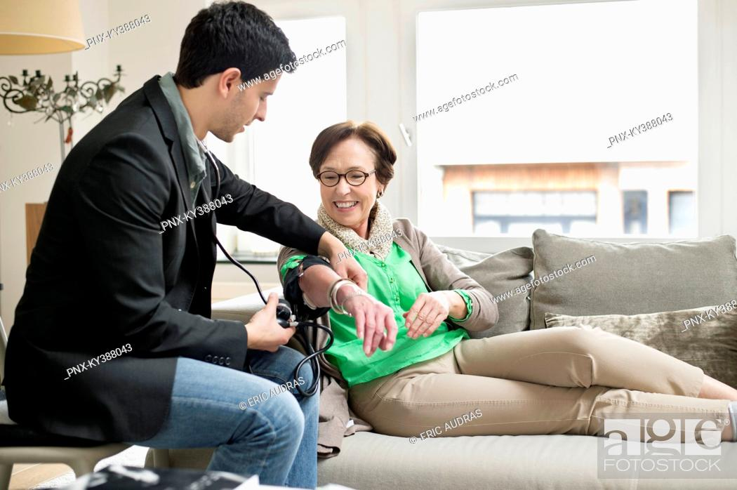 Stock Photo: Male doctor examining a patient with stethoscope.