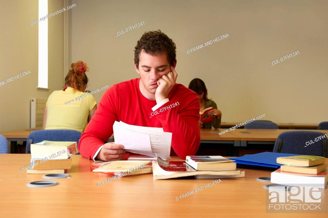 Stock Photo: Bored young man seated at desk studying.