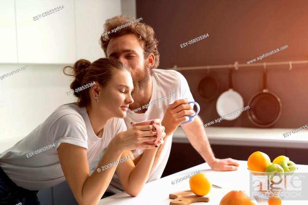 Photo de stock: Morning coffee and gentle kissing feeding each other making fun at modern kitchen and smiling while cooking at home. Pretty girl feeds or nursing her boyfriend.