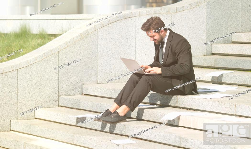 Imagen: Toned picture of businessman in black business suit using laptop computer while sitting n city centre. Freelnace concept.