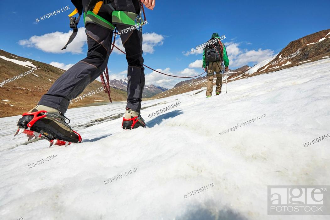 Stock Photo: Young couple hiking up ice on Val Senales Glacier, Val Senales, South Tyrol, Italy.