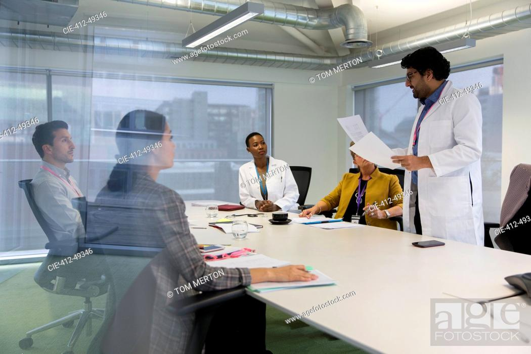 Stock Photo: Male doctor leading conference room meeting.