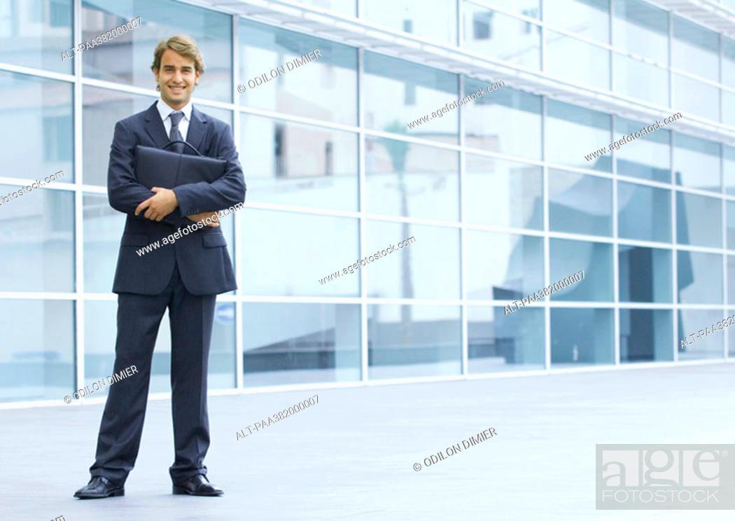 Stock Photo: Businessman holding briefcase, full length portrait.