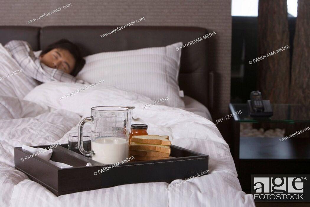 Imagen: Man sleeping in bed, breakfast setting aside.