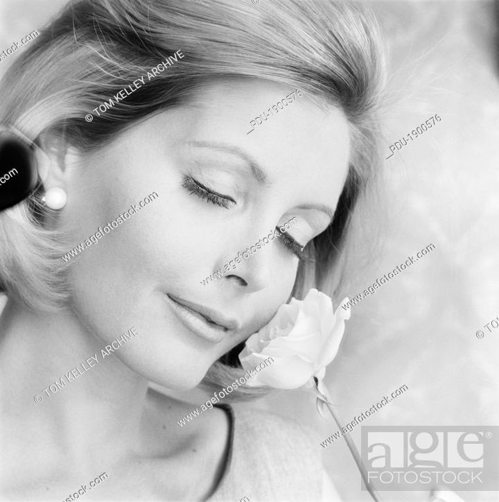 Stock Photo: Young woman holding flower, smiling, close-up.