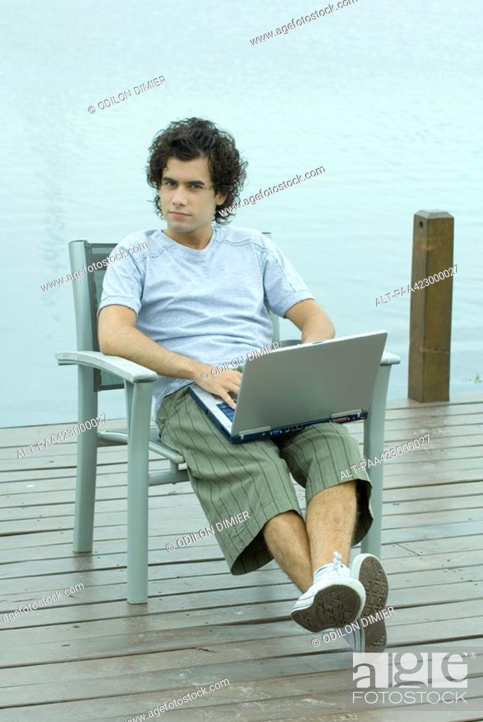 Stock Photo: Young man sitting on dock using laptop, full length.
